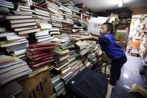 In this Aug. 19, 2015 photo, Cristian Orjuela, 5, looks for a book at Jose Alberto Gutierrez's home in Bogota, Colombia. Garbage collector Gutierrez started rescuing books from the trash almost 20 years ago, when he was driving a garbage truck at night through the capital's wealthier neighborhoods. (AP Photo/Fernando Vergara)